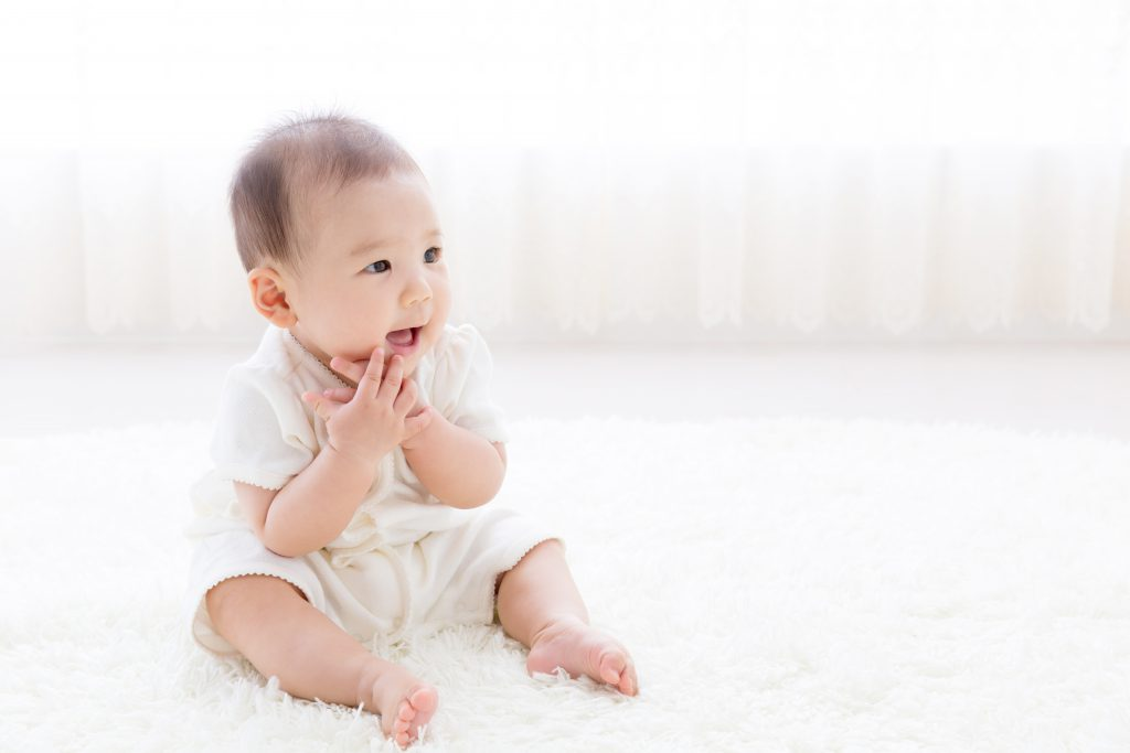 asian baby relaxing on the carpet